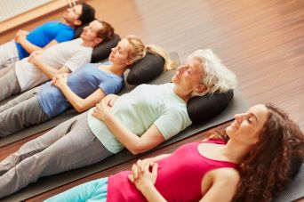 74163556 - senior with a group meditating at fitness center